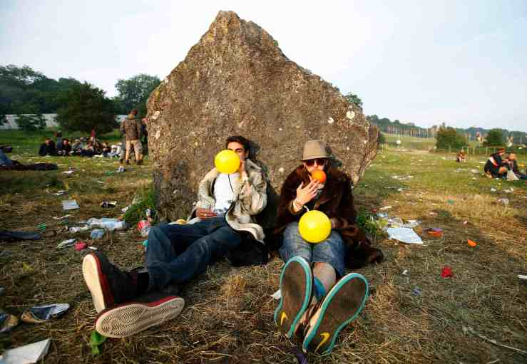 Festival goers inhale laughing gas at sunrise at the stone circle on the second day of Glastonbury music festival at Worthy Farm in Somerset